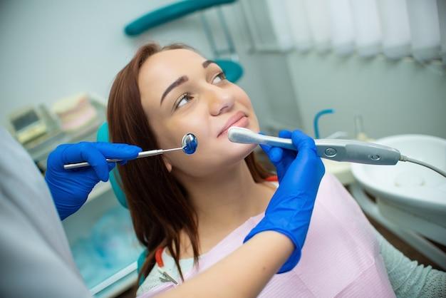 Bella ragazza con i capelli rossi è seduto sulla poltrona del dentista