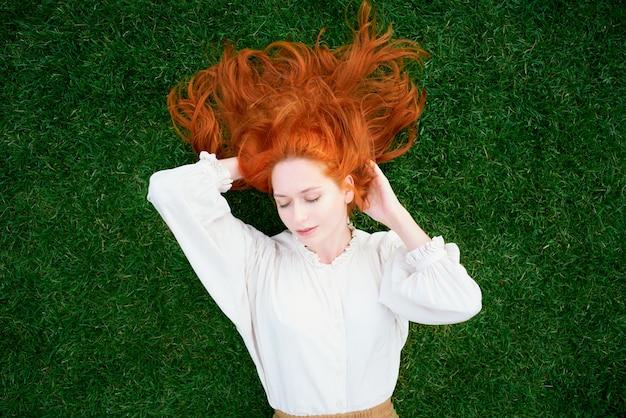 Bella ragazza con i capelli rossi sdraiati sull'erba verde con gli occhi chiusi
