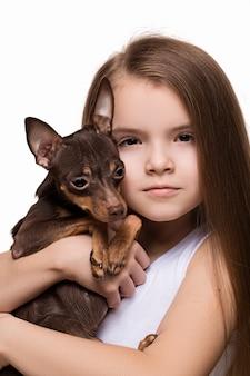 Bella ragazza con il cane sveglio del terrier, isolato su bianco.