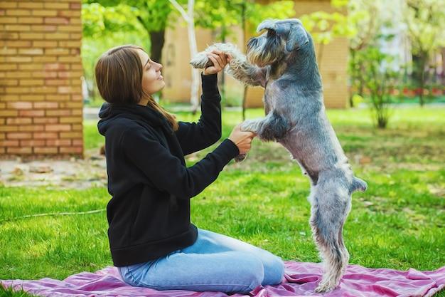 Bella ragazza con il suo cane schnauzer al parco naturale
