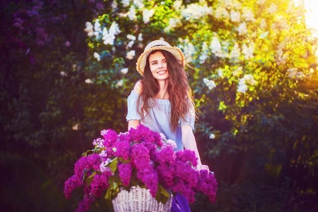 Bella ragazza con la bicicletta d'annata e fiori sulla città backgroundd alla luce solare all'aperto.