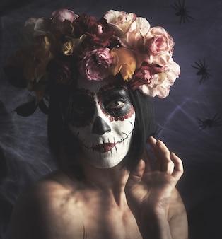 Bella ragazza con la tradizionale maschera di morte messicana.
