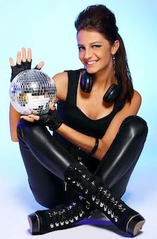 Bella ragazza con le cuffie e la palla da discoteca