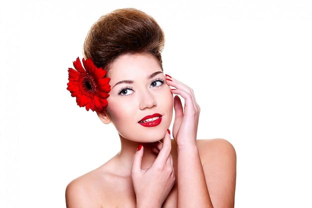 Bella ragazza con le labbra rosse fiorisce sui suoi capelli