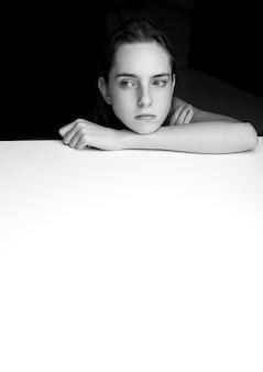 Bella ragazza con le mani eleganti sul cubo bianco su sfondo nero