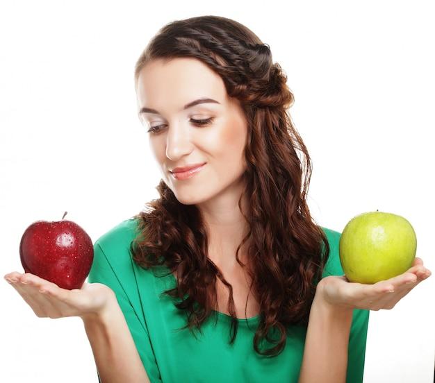 Bella ragazza con le mele rosse e verdi