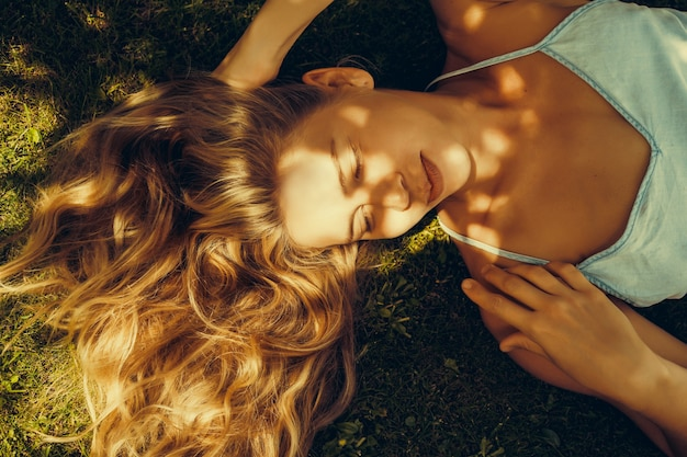 Bella ragazza con lunghi capelli bianchi si trova sull'erba verde e sorride. strizzare gli occhi. un occhio ristretto e un sorriso maledetto.