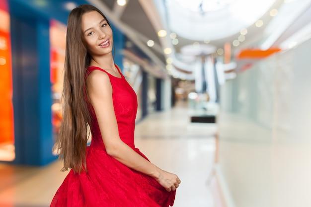 Bella ragazza con lunghi capelli castani in abito rosso