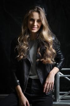Bella ragazza con lunghi capelli ricci in giacca di pelle nera, t-shirt e jeans