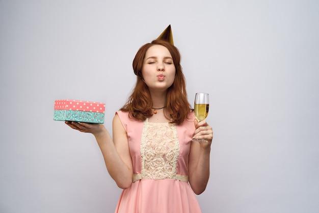 Bella ragazza con lunghi capelli rossi in possesso di un bicchiere di champagne e confezione regalo. lei socchiuse gli occhi e manda un bacio
