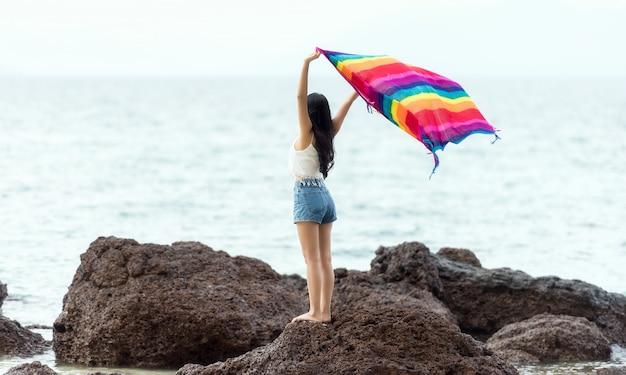 Bella ragazza con sciarpa colorata sulla spiaggia. viaggi e vacanze.