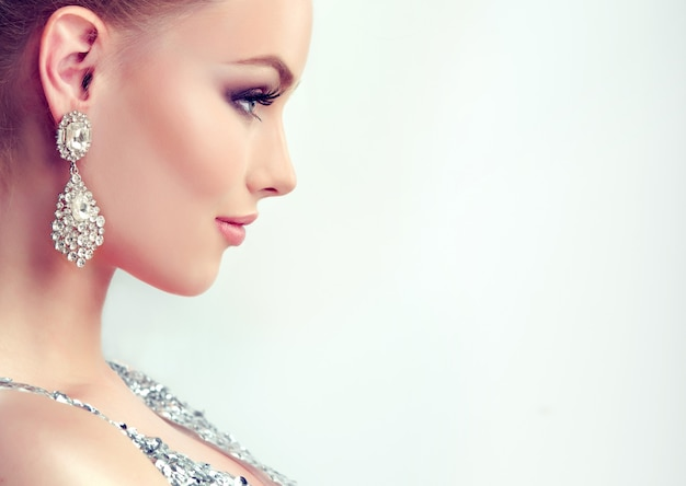 Bella ragazza con trucco da sera e orecchini grandi gioielli