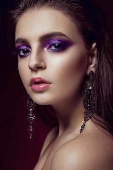 Bella ragazza con trucco e gioielli viola luminosi.