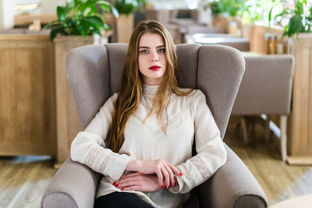 Bella ragazza con trucco professionale e acconciatura seduta nel ristorante.