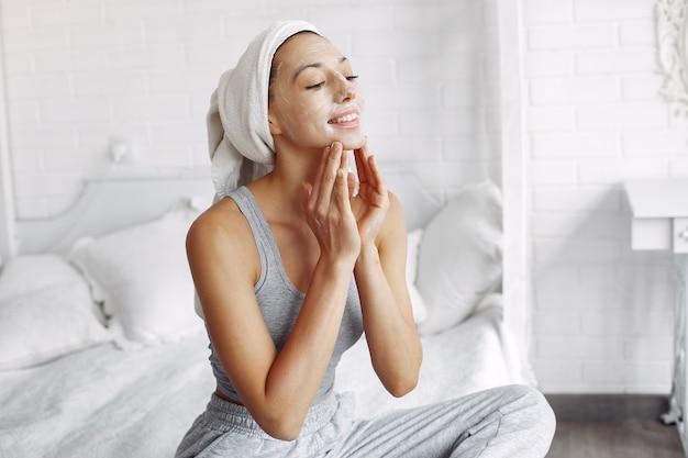 Bella ragazza con un asciugamano usando un prodotto di bellezza