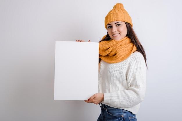 Bella ragazza con un bel sorriso alzando un foglio di carta bianco