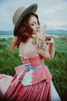 Bella ragazza con un coniglio all'aperto in una giornata estiva