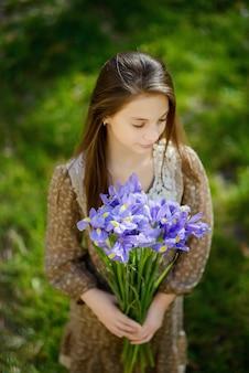 Bella ragazza con un mazzo di iris viola viola nelle sue mani
