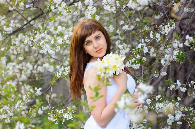 Bella ragazza con un mazzo di narcisi in un vestito bianco