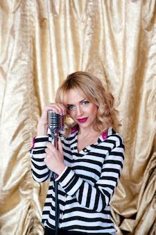 Bella ragazza con un microfono in un abito a righe.