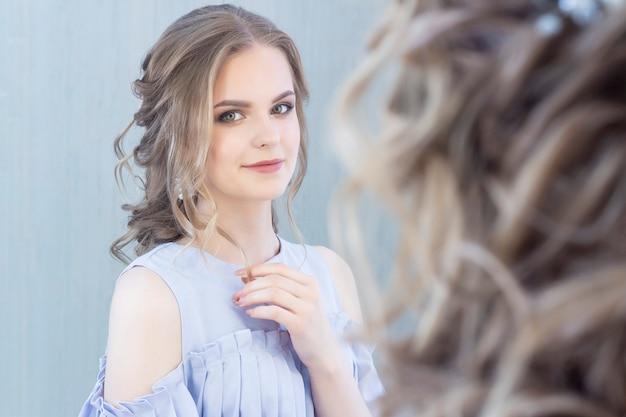 Bella ragazza con un taglio di capelli da sposa si guarda allo specchio, ritratto di una giovane ragazza. bellissimo trucco. salone di bellezza