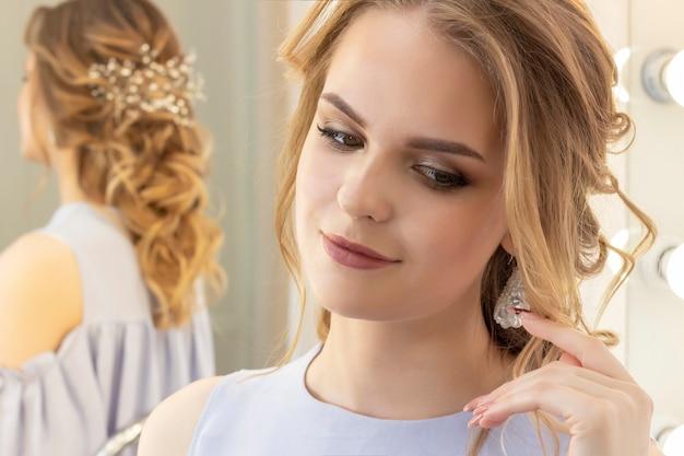 Bella ragazza con un taglio di capelli da sposa si guarda allo specchio, ritratto di una giovane ragazza. bellissimo trucco.