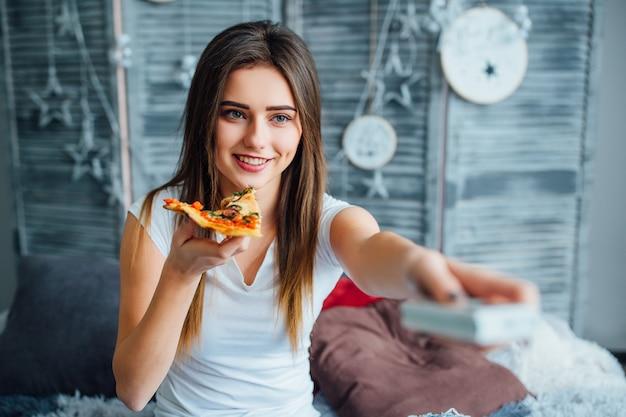 Bella ragazza con una fetta di pizza e console sulla sua mano ha un weekend a casa.