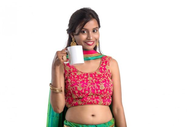 Bella ragazza con una tazza di tè o caffè in posa sulla superficie bianca