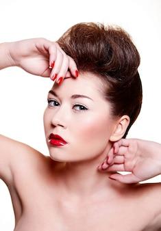 Bella ragazza con unghie e labbra rosse