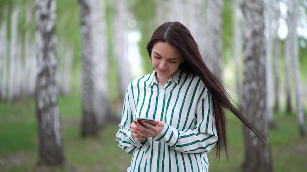 Bella ragazza con uno smartphone in mano cammina lungo un boschetto di betulle in primavera.