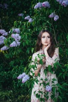 Bella ragazza dagli occhi grandi vicino all'albero lilla.