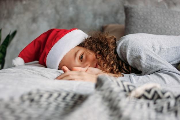 Bella ragazza dai capelli riccia del tween in cappello di santa e pigiami che si siedono sul letto con il cuscino, tempo di mattina di natale