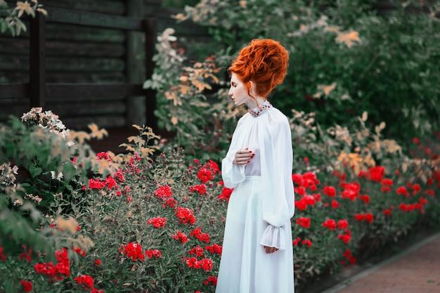 Bella ragazza dai capelli rossi con i capelli alti in un vecchio abito bianco nel parco. l'era vittoriana. costume storico. regina bianca. castello principessa