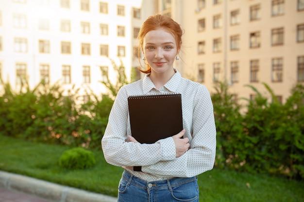 Bella ragazza dai capelli rossi con le lentiggini che abbracciano notebook