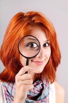 Bella ragazza dai capelli rossi con lente di ingrandimento zoomando i suoi occhi.