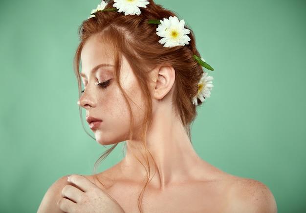 Bella ragazza dai capelli rossi positiva con una corona di camomilla in testa