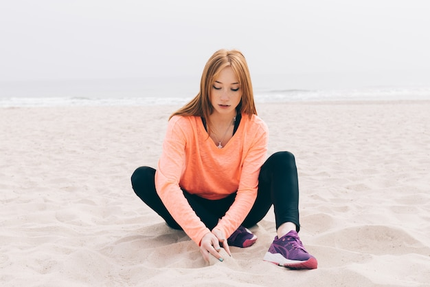 Bella ragazza dai capelli rossi, seduta sulla spiaggia
