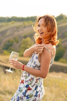 Bella ragazza dai capelli rossi si diverte e balla in un campo al tramonto