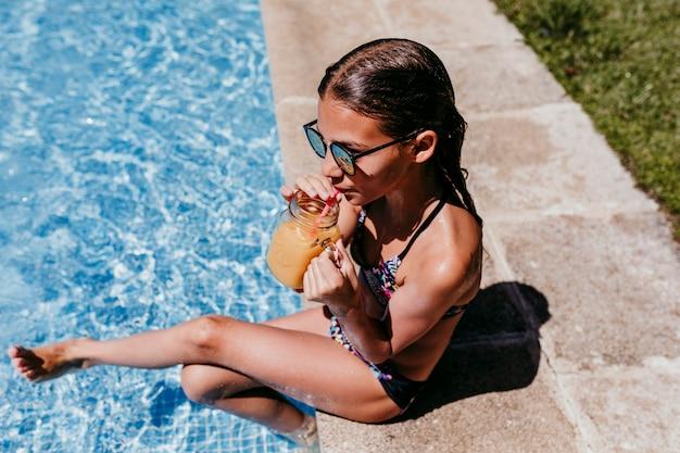 Bella ragazza dell'adolescente allo stagno che beve il succo di arancia sano e che si diverte all'aperto. concetto di estate e stile di vita