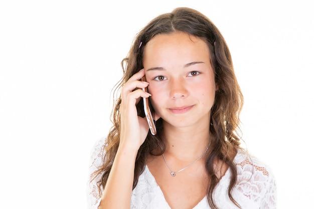 Bella ragazza dell'adolescente che parla sul telefono nello studio nel fondo bianco