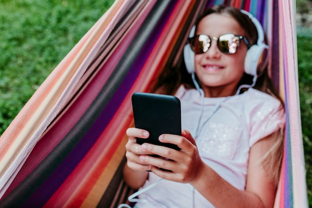 Bella ragazza dell'adolescente che si trova sull'amaca variopinta al giardino. ascoltare la musica sul cellulare e sull'auricolare e sorridere