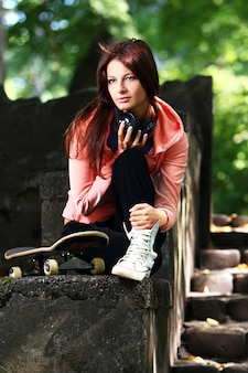 Bella ragazza dell'adolescente con le cuffie nel parco