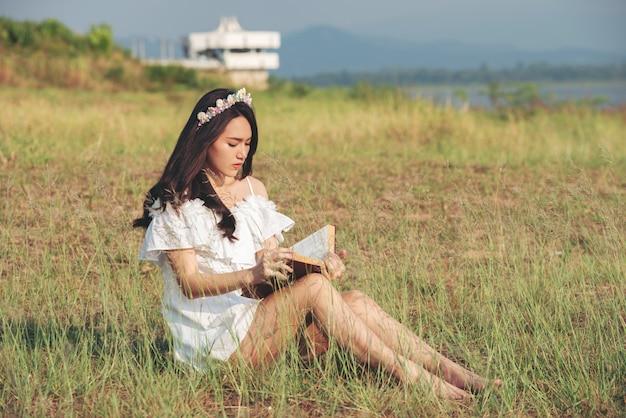 Bella ragazza dell'asia al campo di erba che legge un libro coperto