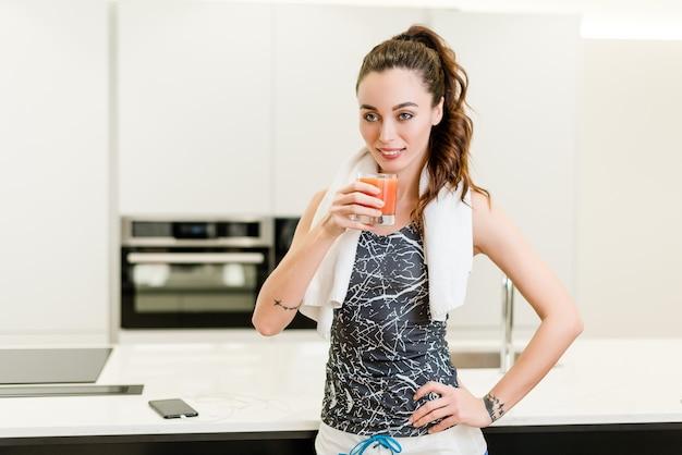 Bella ragazza di forma fisica che beve succo fresco alla cucina