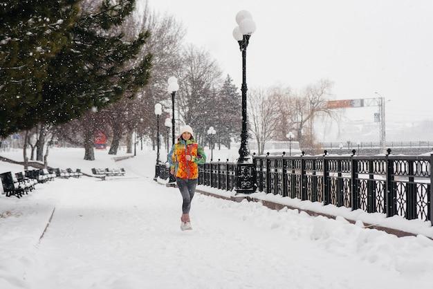 Bella ragazza è fare jogging in una giornata gelida e nevosa. sport, stile di vita sano