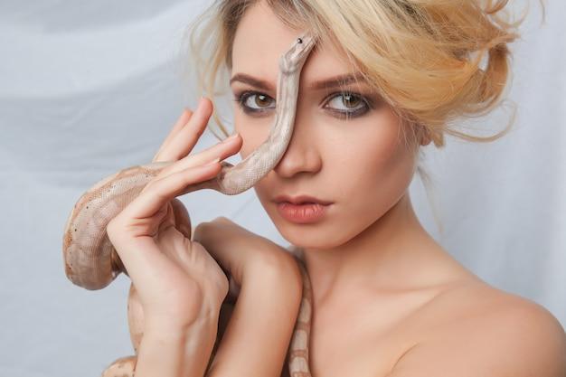 Bella ragazza e il serpente boa constrictor, che le avvolge il viso