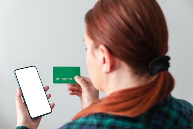 Bella ragazza effettua pagamenti online utilizzando uno smartphone e una carta di credito per lo shopping a casa.