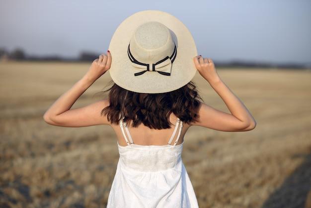 Bella ragazza elegante in un campo di grano in autunno