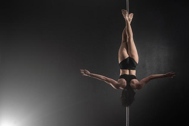 Bella ragazza esile con il pilone, ballerino femminile del palo che balla su un fondo nero