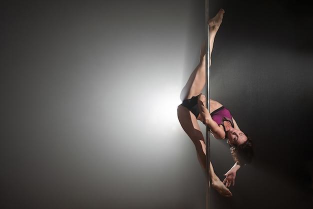 Bella ragazza esile con pilone. ballerino femminile del palo che balla su un fondo nero